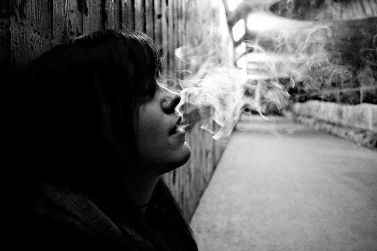 Woman smoking by wall