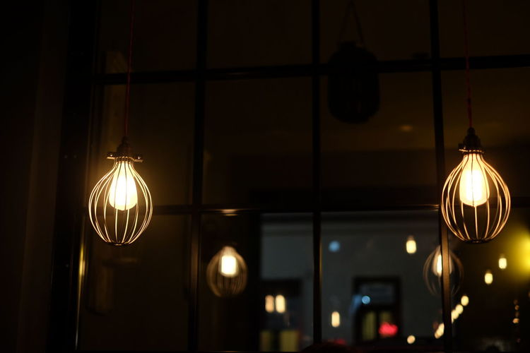Low Angle View Of Illuminated Light Bulbs Against Window