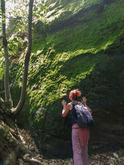Rear view of woman standing in forest, touching and smelling moss