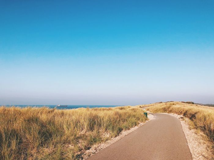 Scenic View Of Road By Sea Against Clear Blue Sky
