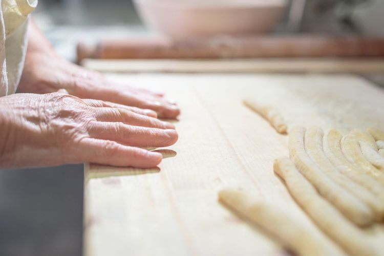 Cropped hands rolling dough at table in kitchen
