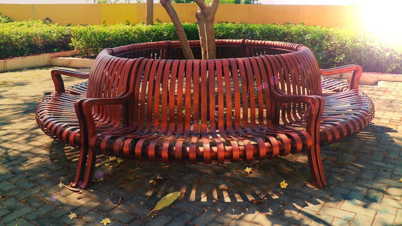 EMPTY BENCH IN PARK AGAINST TREES