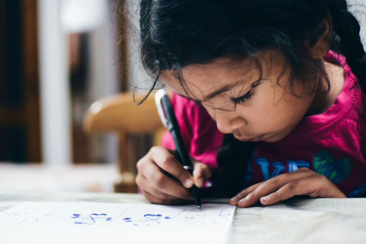 Close-Up Of Girl Drawing On Table