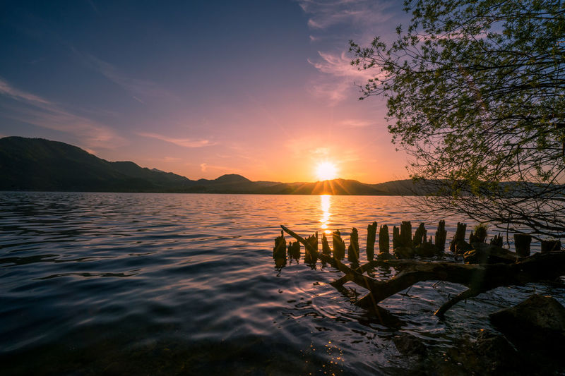 Austria ❤ EyeEm Best Shots EyeEm Nature Lover Beauty In Nature Cloud - Sky Idyllic Mountain Nature Non-urban Scene Orange Color Outdoors Real People Reflection Scenics - Nature Sea Silhouette Sky Sun Sunset Tranquil Scene Tranquility Traunsee Water Waterfront Wooden Post