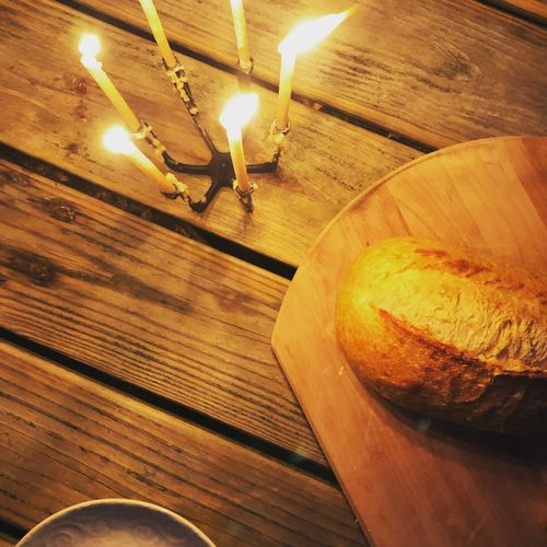 High angle view of lit candles on wooden table