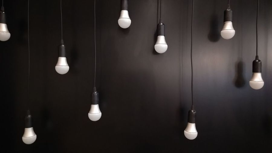 Light bulbs hanging against black wall