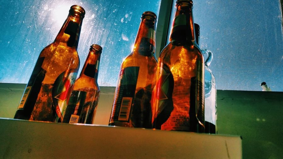 Low angle view of bottles on glass against sky