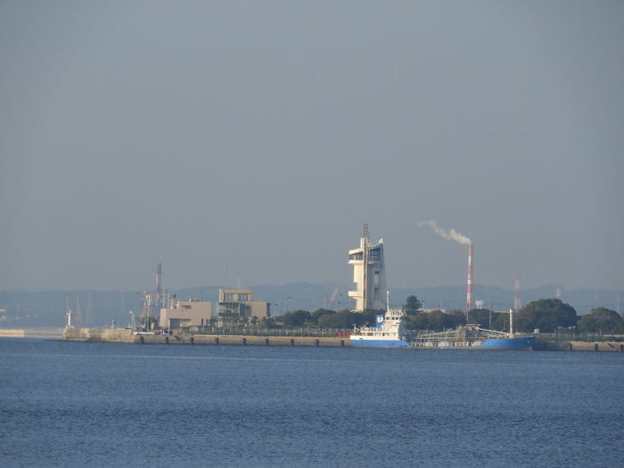 View of factory by sea against clear sky