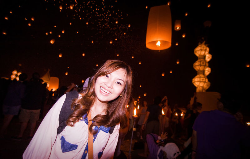 Portrait of smiling woman standing against paper lanterns at night