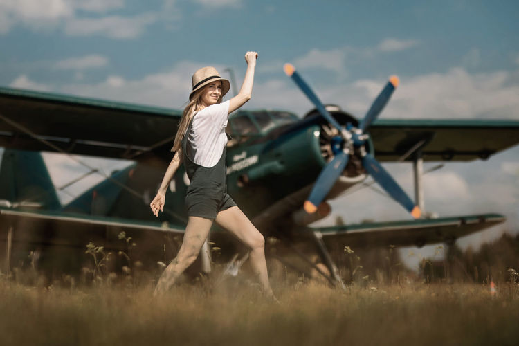 A woman walks on the airfield in the background of the plane