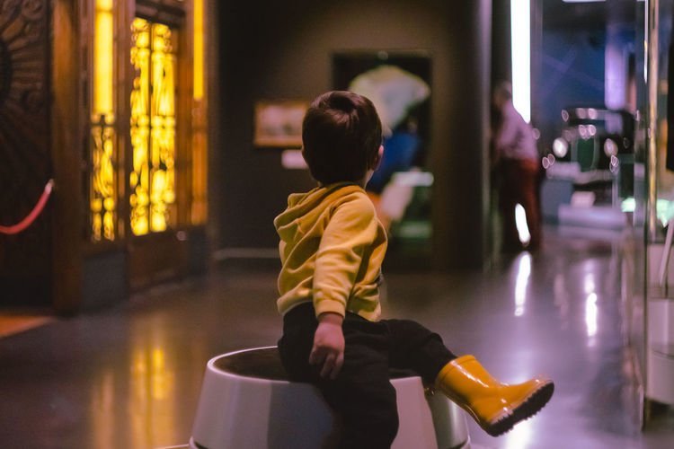 Little boy climbing on to a round bench in the Museum TerribleTwos Toddler  Climbing Indoors  Rear View Incidental People Real People Lifestyles One Person Leisure Activity