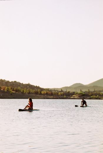 People on boat in lake against clear sky
