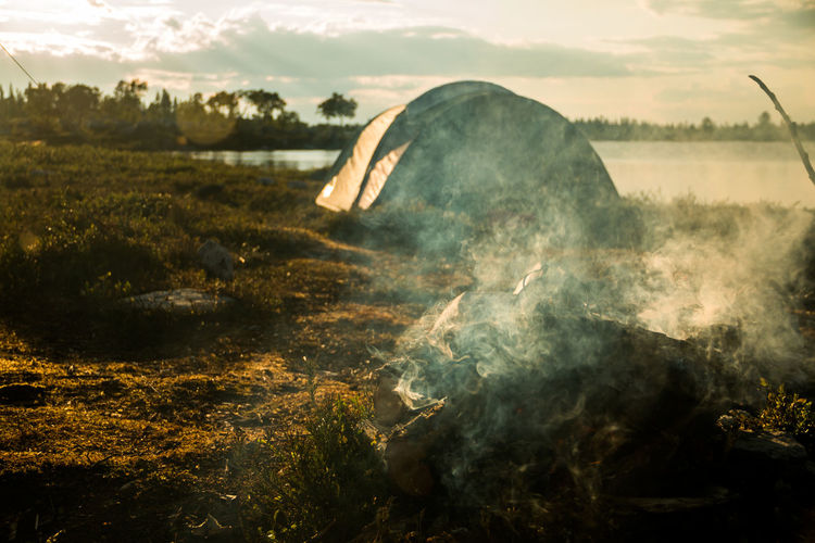 Smoke from campfire by tent at lakeshore during sunset