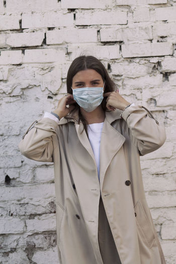 A girl dressed in warm white clothes, standing against a brick wall puts on a medical  mask