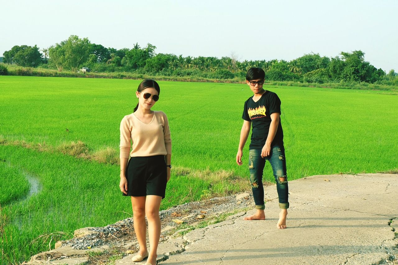 field, green color, casual clothing, grass, real people, full length, front view, landscape, two people, tree, day, standing, togetherness, young adult, leisure activity, young women, growth, outdoors, lifestyles, agriculture, nature, sky, adult, people