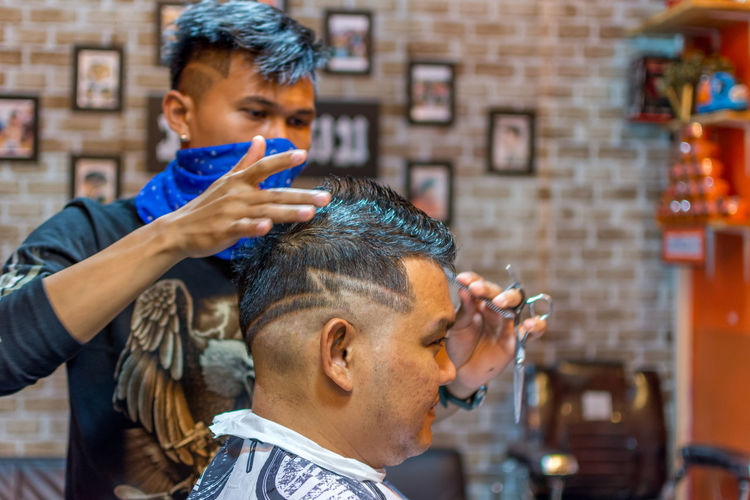 Barber Barber Shop Body Care Close-up Combing Customer  Cutting Hair Day Hair Care Hairdresser Hairstyle Headshot Human Hair Indoors  Lifestyles Men Occupation Preparation  Razor Real People Skill  Small Business Two People Working Young Adult