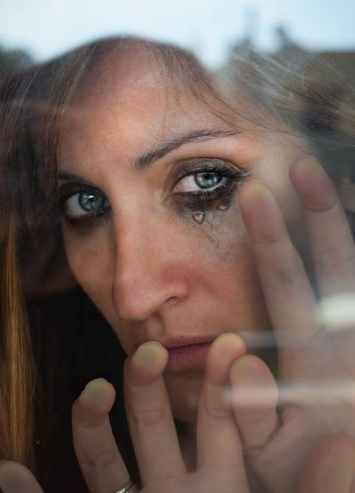 Close-up portrait of depressed woman seen through glass window