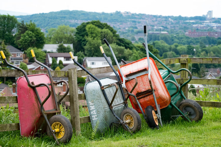 Four upturned wheelbarrows in a field with backdrop of Oldham town, with cotton mills. Four Grass Green Color Trees Wheelbarrow Landscape Metal No People Oldham Oldhamcounty Outdoors Tool Wheels