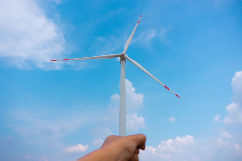 Alternative Energy Body Part Cloud - Sky Day Environment Environmental Conservation Finger Hand Holding Human Body Part Human Hand Human Limb Low Angle View Nature One Person Outdoors Power In Nature Renewable Energy Sky Wind Power Wind Turbine