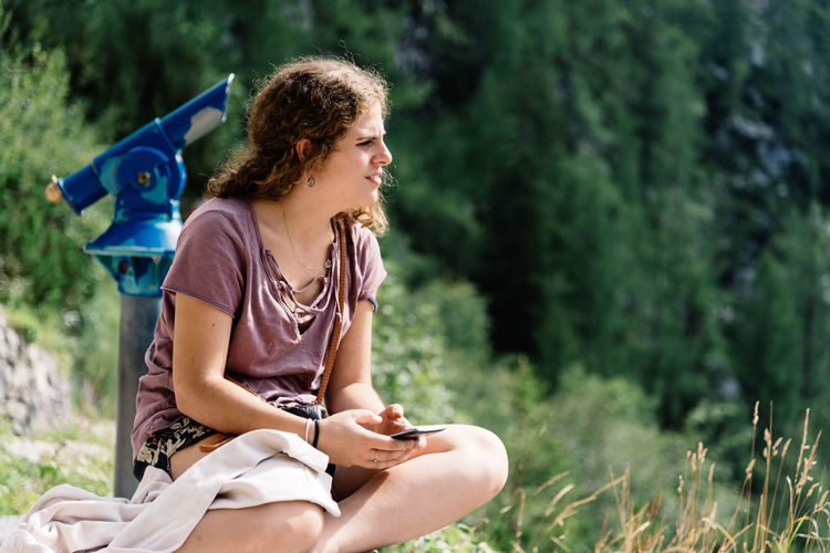 Beautiful young woman sitting texting on smartphone in nature Nature Sitting Adult Beautiful Woman Casual Clothing Curly Hair Day Focus On Foreground Forest Girl Grass Holding Leisure Activity Lifestyles Nature One Person One Young Woman Only Outdoors People PhonePhotography Real People Sitting Smartphone Smiling Technology Texting Tree Wireless Technology Young Adult Young Women