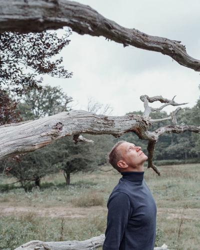 Man standing by tree on field
