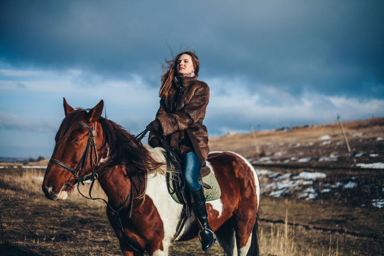 Woman riding horse on land against cloudy sky