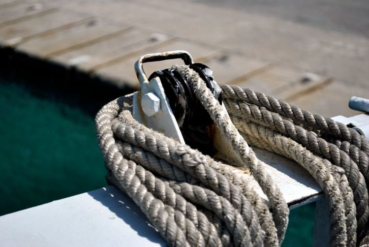 Close-up of rope tied to boat moored at harbor