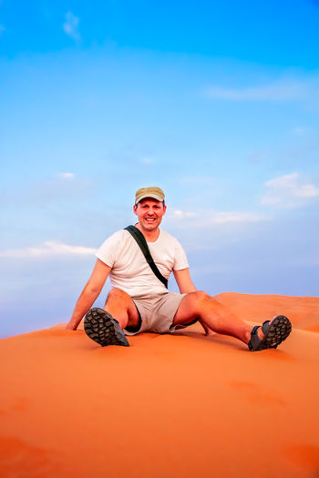 Portrait of happy man sitting on sand dune against sky