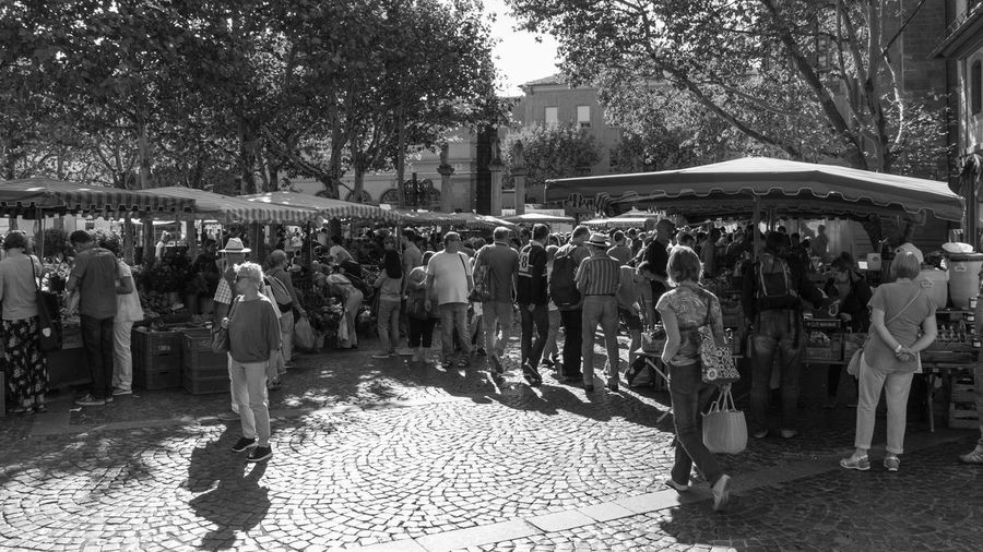 16:9 Market B&w Black Black And White City Day Group Of People Lifestyles Market Stall Marketplace Men Outdoors People Real People Street Street Market Streetphotography Sunny Day Tree Walking Weekly Market White Women