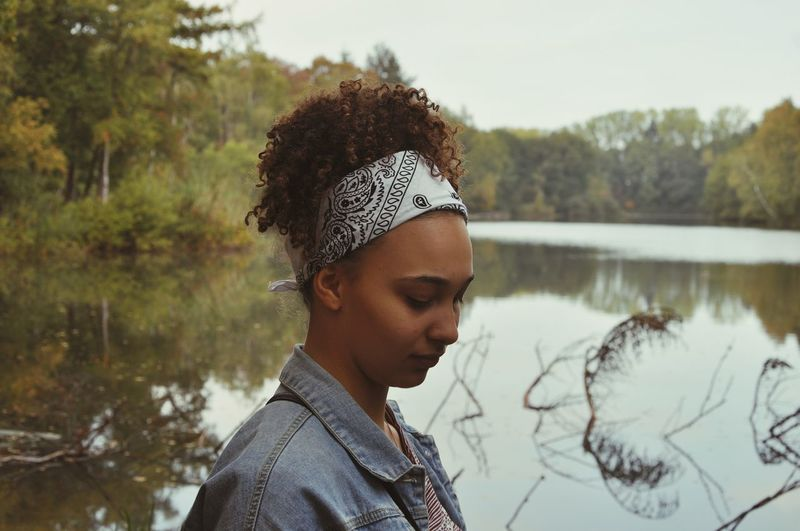 Side view of teenage girl standing against lake in forest