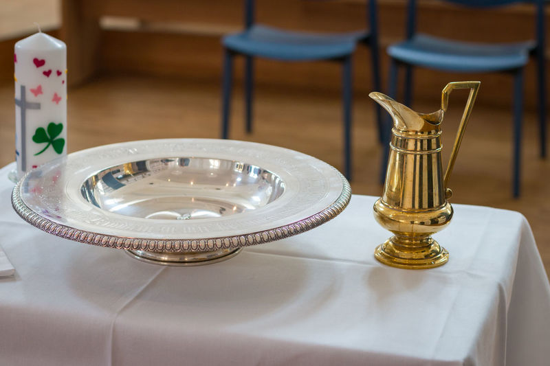 Prepared table for baptism with baptismal jug, bowl and candle Table Indoors  Seat No People Focus On Foreground Furniture Chair Plate Tablecloth Close-up Candle Still Life High Angle View Setting Religion Christianity Baptism Jug Baptismal Font Font Preparation  Faith Belief Ceremony Golden