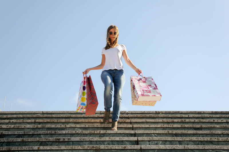 Low angle view of young woman holding shopping bags while walking on staircase against clear sky