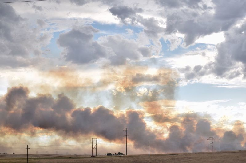 Smoke over field against sky
