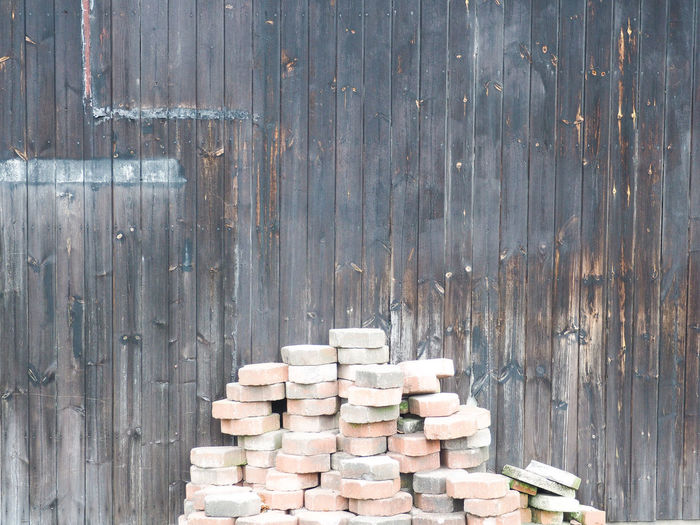 Stack of paving blocks arranged against wooden wall
