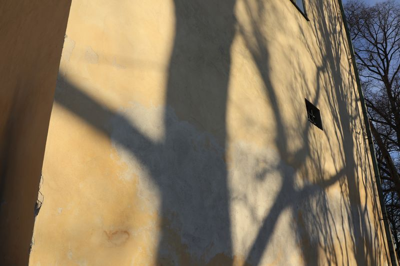 High angle view of shadow of fence on wall