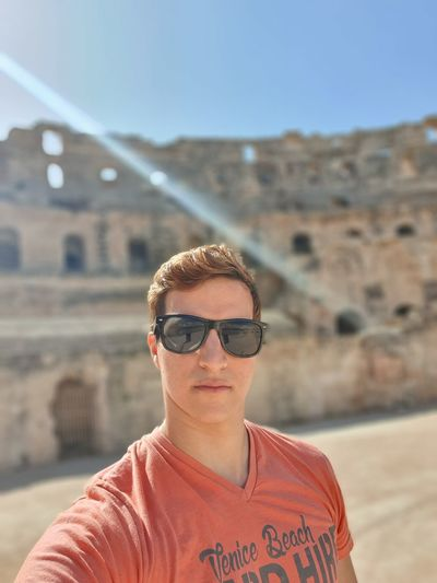 Portrait of young man wearing sunglasses standing against old ruins