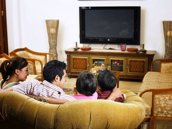 Rear View Of Family Sitting On Sofa At Home