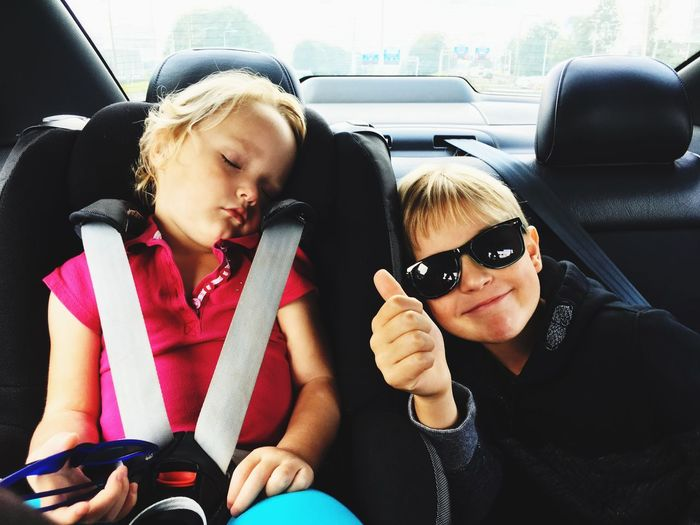 Portrait of boy wearing sunglasses with sister in car