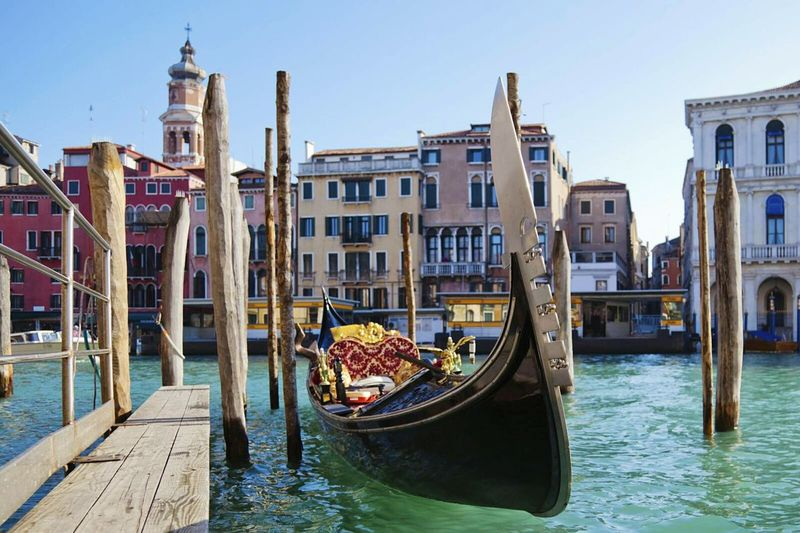 Gondola moored in grand canal against sky