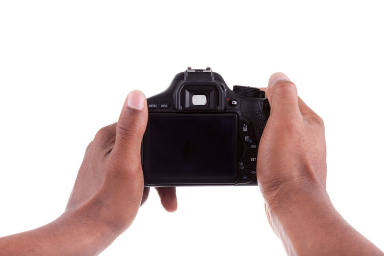 Close-up of hand holding camera against white background