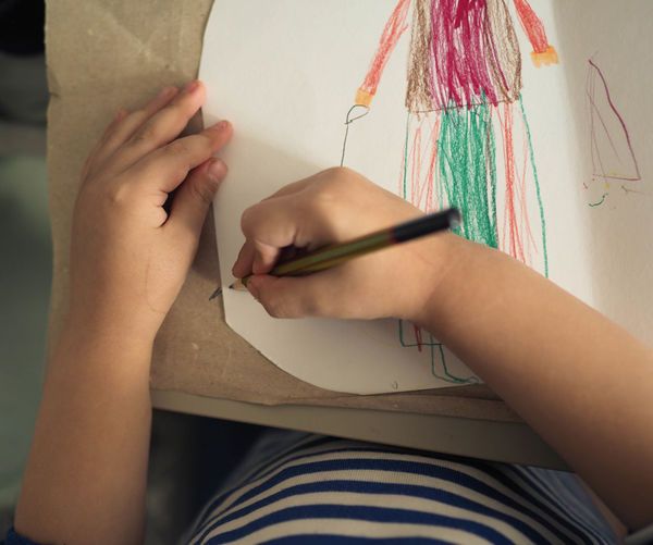 High angle view of girl drawing on paper