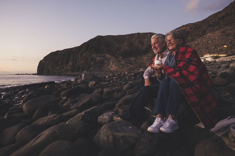 Senior couple looking at the sunset in vacation time join freedom and tenderly. Two elderly model caucasian with white hair. Hug Love Day Lifestyles Looking At View Men Mountain Nature Ocean Outdoors People Real People Sea Senior Couple Sheet Sky Tenderly Togetherness Togetherness Friendship Two People Vacations Warm Clothing Water White Hear Women