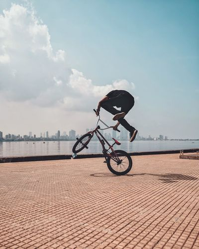 Man bmx cycling on promenade in city against blue sky