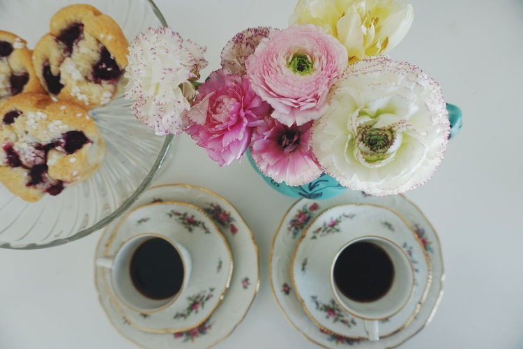 Directly Above Shot Of Coffee Cup And Flower Vase On Table