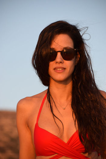 Beautiful young woman on the beach Beach Photography Dark Hair Adult Beautiful Woman Fashion Front View Glasses Hair Hairstyle Happiness Leisure Activity Lifestyles Long Hair Looking At Camera One Person Portrait Sand Sky Smiling Summer Sunglasses Swimwear Women Young Adult Young Women