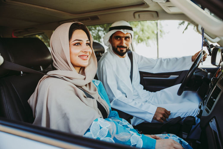 Couple wearing traditional clothing sitting in car