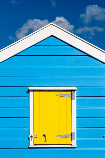 A Beach Hut Architecture Beach Hut Blue Building Exterior Buildings Built Structure Cloud - Sky Coastal Day No People Outdoors Seaside Shutter Sky Southwold Vertical Window Wood - Material Yellow