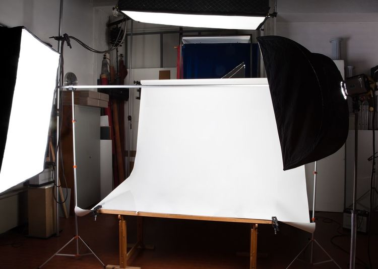 Backdrop Amidst Illuminated Lighting Equipment At Studio