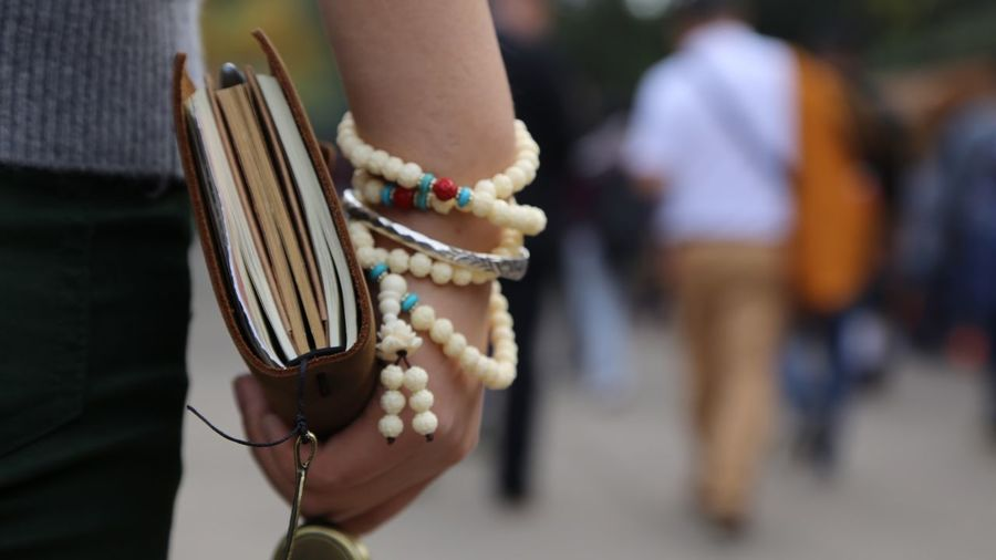 Close-up Of Person Carrying Religious Book And Rosary Beads