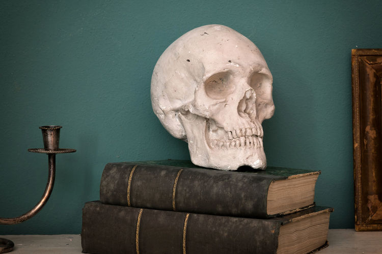 Close-up of skull on old books against wall